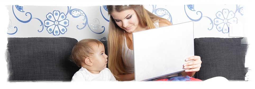 Mom and baby on couch, mom is using laptop